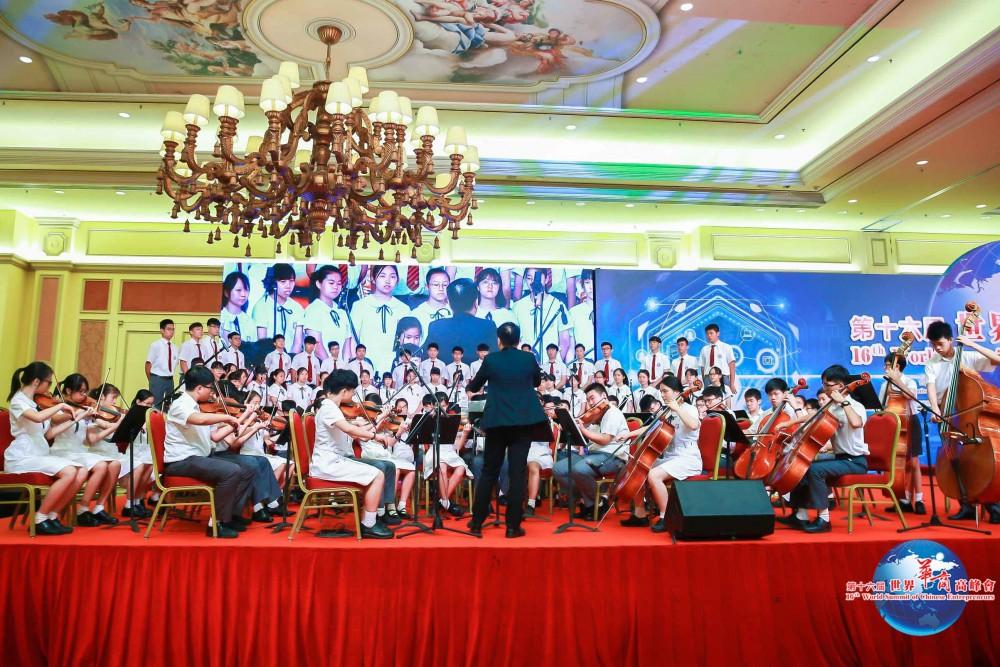 第十六屆世界華商高峰會開幕典禮-澳門培正中學管弦樂團及歌詠隊在開幕典禮上演唱《華商頌》。
